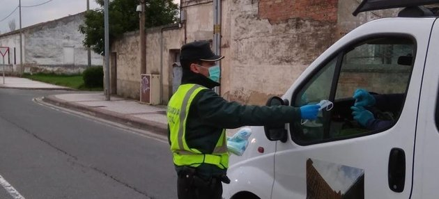 Un guardia civil reparte mascarillas.