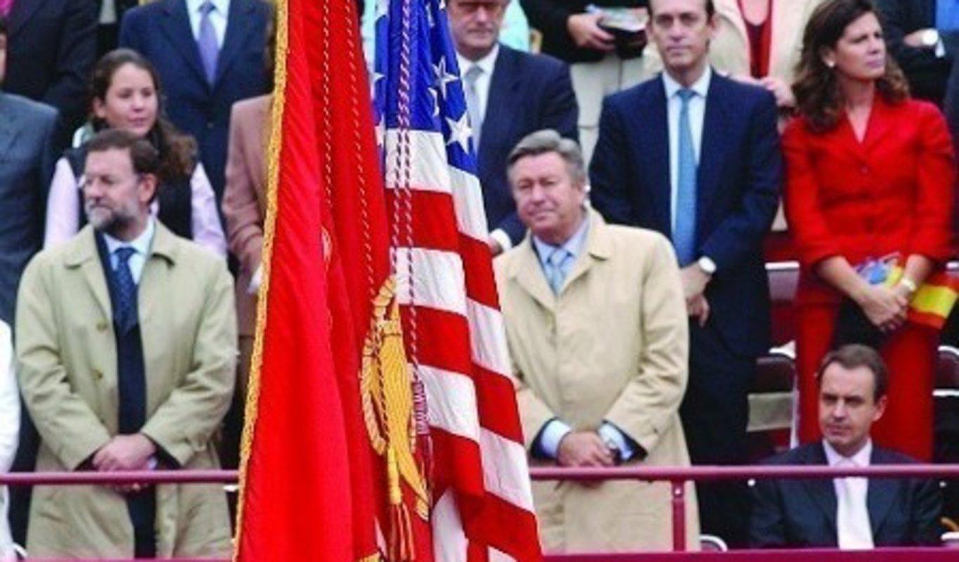 Zapatero sentado al paso de la bandera de USA.
